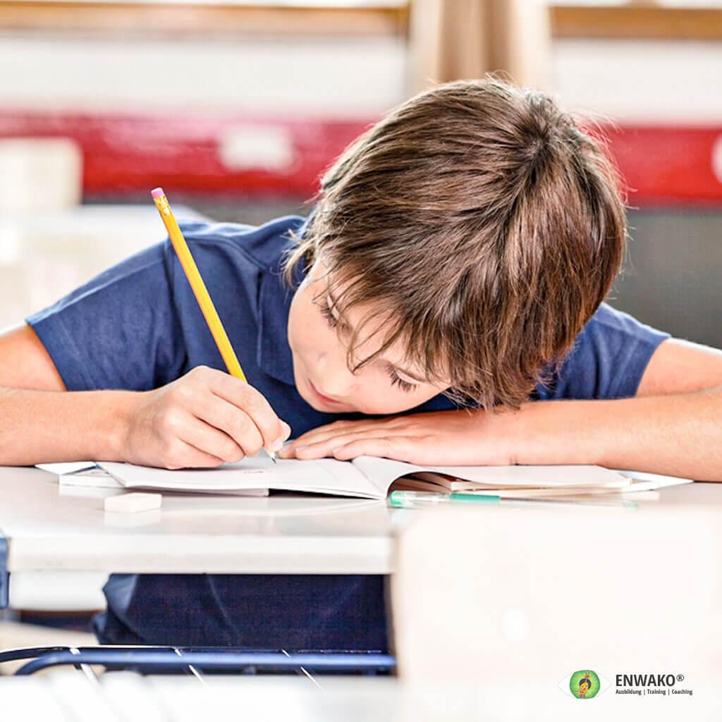 Kind schreibt in Buch